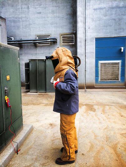 Electrical Testing and Maintenance expert in gear in front of a electrical box